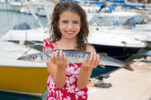 Happy kid fisherwoman with barracuda fish catch — Stock Photo