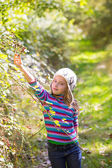 Kid winter girl picking mulberry berries in the forest — Stock Photo