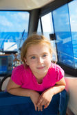 Blond kid girl at boat indoor sailing smiling happy — Stock Photo