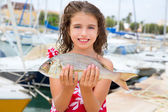 Happy kid fisherwoman with dentex fish catch — Stock Photo