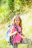 Explorer kid girl walking with backpack in grass — Stock Photo