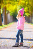Autumn winter kid girl blond with jeans and pink snow cap — Stock Photo