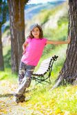 Kid girl with camouflage pants and cap in park bench outdoor — Stock Photo