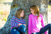 Sister kid girls smiling sit relaxed in a oak tree trunk — Stock fotografie