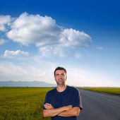 Mid age man in road at meadows posing crossed arms — Stock Photo