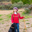 Stock Photo: Kid girl shepherdess happy with dog and flock of sheep