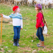 Stock Photo: Kid girl shepherdess sisters happy with flock of sheep and stick