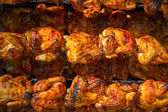 Roasted chicken in a row turning on a roaster — Stock Photo