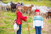 Kid girl shepherdess sisters happy with flock of sheep and stick — Stock Photo