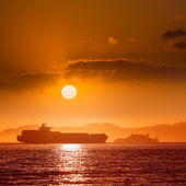 Alcatraz island penitentiary at sunset and merchant ship — Stock Photo