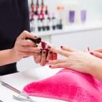 Nail saloon woman painting color nail polish in hands — Stock Photo #40197501