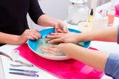 Nail saloon scrub bath exfoliant hands in bowl water — Stock Photo