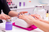 Nails saloon woman nail polish remove with tissue — Stock Photo