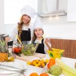 Kid girls junior chef friends hug together in countertop — Stock Photo #41037935