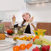Blond kind girl junior chef on countertop salad — Stock Photo