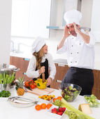 Funny chef master and junior kid girl at cooking school crazy — Stock Photo