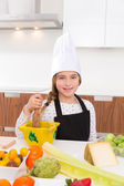 Blond kind girl junior chef on countertop — Stock Photo