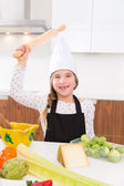 Kid girl chef on countertop funny gesture with roller knead — Stock Photo