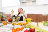 Blond kind girl junior chef on countertop salad — Stockfoto