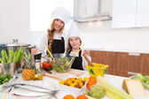 Kid girls junior chef friends hug together in countertop — Stock Photo
