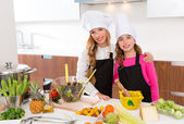 Kid girls junior chef friends hug together at cooking school — Stock Photo