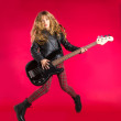 Blond Rock and roll girl with bass guitar jump on red — Stock Photo #41040805