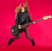 Blond Rock and roll girl with bass guitar jump on red — Stock Photo