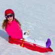 Kid girl playing sled in winter snow — Stock Photo #41768359