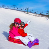 Kid girls playing sled in winter snow — Stock Photo