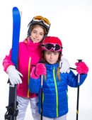 Siters kid girls with ski poles helmet and snow goggles — Stock Photo