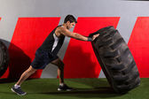 man flipping a tractor tire workout gym exercise — Stock Photo