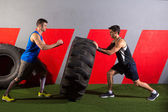men flipping a tractor tire workout gym exercise — Stock Photo
