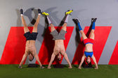Handstand push-up group workout at gym — Stock Photo