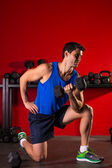 Hex dumbbells man workout in red gym — Stock Photo