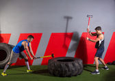 Sledgehammer Tire Hits men workout at gym — Stock Photo