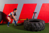 Sledgehammer Tire Hits woman workout at gym — Stock Photo