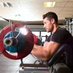 Biceps preacher bench arm curl workout man at gym — Stock Photo #47220499