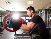 Biceps preacher bench arm curl workout man at gym — Stock Photo