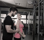 Cable pulley system personal trainer man and woman — Stockfoto