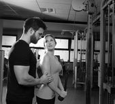 Cable pulley system personal trainer man and woman — Stock fotografie
