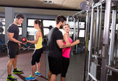 Cable pulley system gym and dumbbell fitness people — Stock Photo