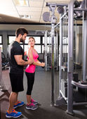 Cable pulley system personal trainer man and woman — ストック写真