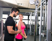 Cable pulley system personal trainer man and woman — Stok fotoğraf