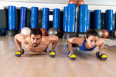 Dumbbells push-ups couple at fitness gym  — Stock Photo