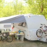 Camping camper caravan trees park bicycles — Stock Photo #5506256