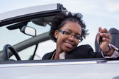 Young black woman driver holding car keys driving her new car — Stock Photo
