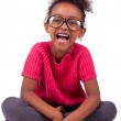Cute young African American girl seated on the floor — Stock Photo #14273875