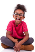 Cute young African American girl seated on the floor — Stock Photo