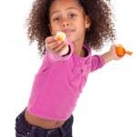Little African Asian girl sharing a tangerine — Stock Photo