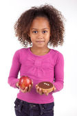 Little African Asian girl hesitating between fruits or candy — Stock Photo